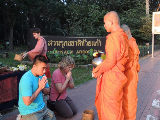 Romey Louangvilay and Shannon Hurst Lane giving alms to monks in Chiang Mai, Thailand